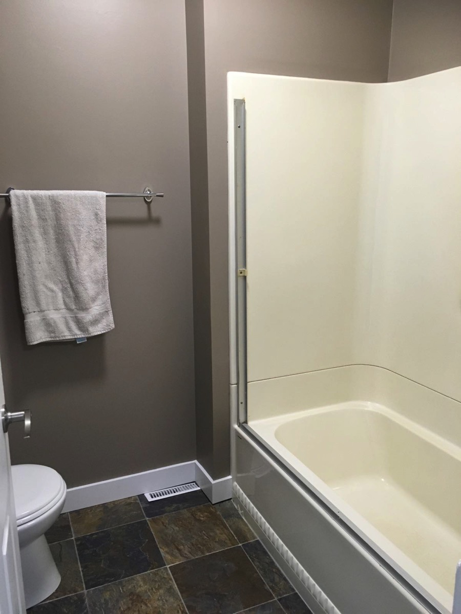 Bathroom is modernized with shower, full tub, sink and toilet